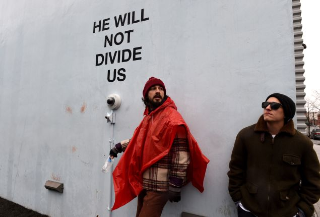 Shia LaBeouf with his performance work, He Will Not Divide Us, outside the Museum of the Moving Image in Astoria, Queens.