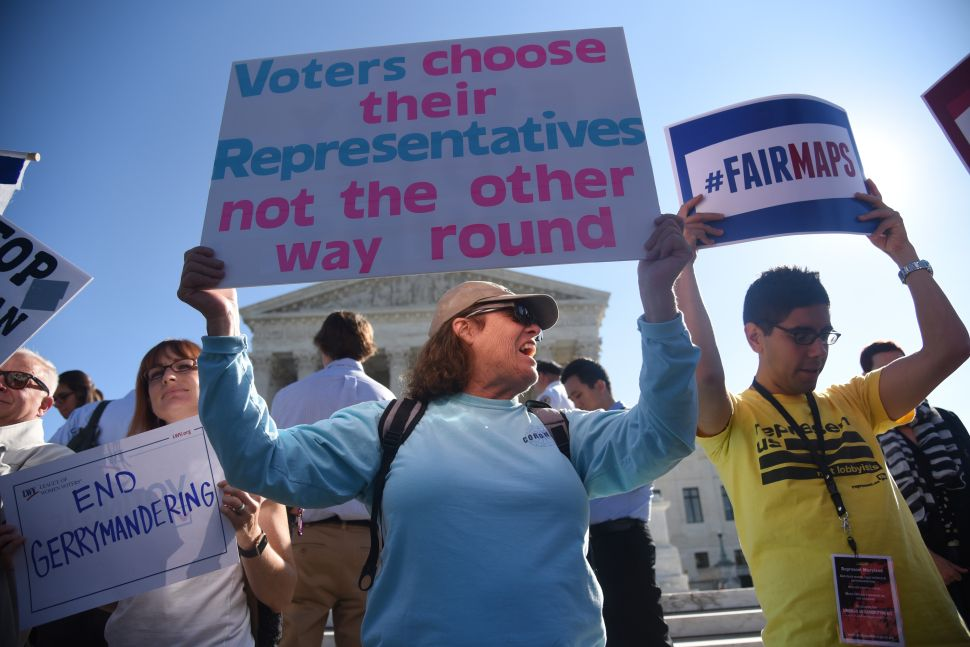 Demonstrators gather outside of the United States Supreme Court during an oral arguments in Gill v. Whitford to call for an end to partisan gerrymandering on October 3, 2017 in Washington, D.C.