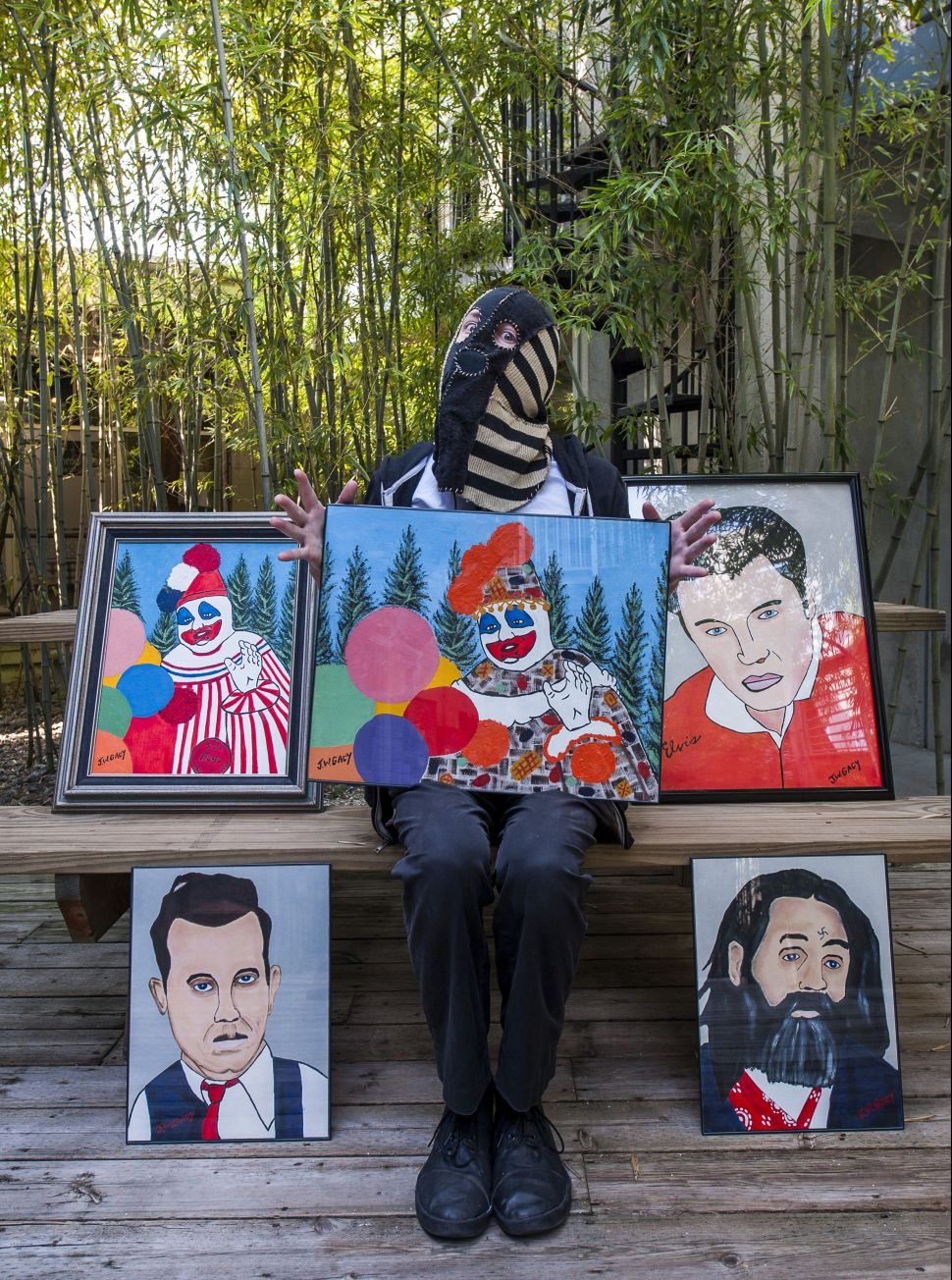 "Ryan Graveface (masked) poses with some of his favorite Gacy paintings, ""He was different to me,"" Graveface says of the serial killer who was executed in 1994. ""No one will ever be more fascinating than Gacy. He was an oddly compelling piece of crap."""