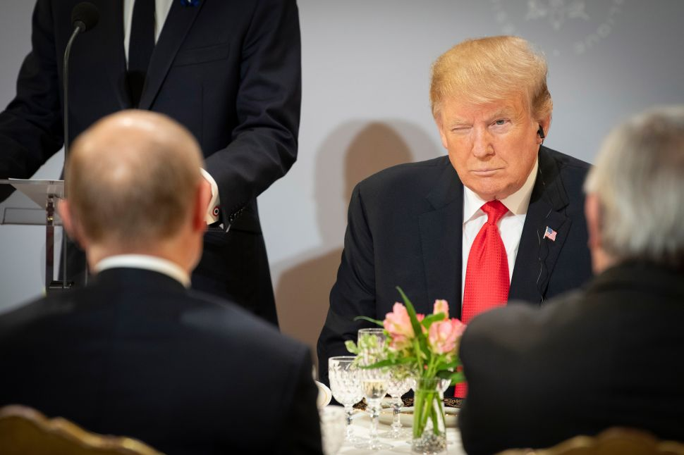 President Donald Trump sits opposite Russian President Vladimir Putin during lunch at the Élysée Palace.