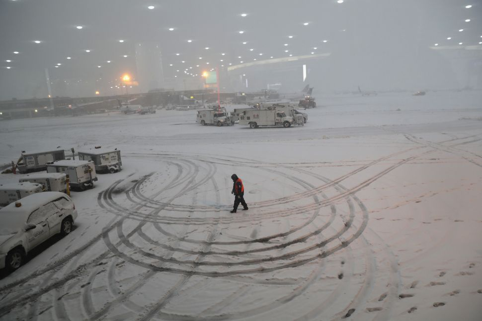 NEWARK, NJ - NOVEMBER 15:  A ground crew member walks through the snow at the Newark Liberty International Airport on November 15, 2018 in Newark, New Jersey. The early season storm caused flight cancellations in much of the northeast.