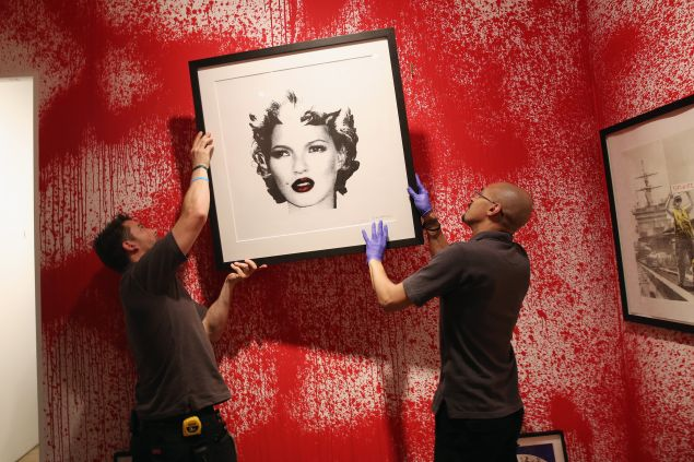 Sotheby's employees hang a print ahead of the first unauthorized retrospective of works by UK artist Banksy on June 6, 2014, curated by Steve Lazarides.
