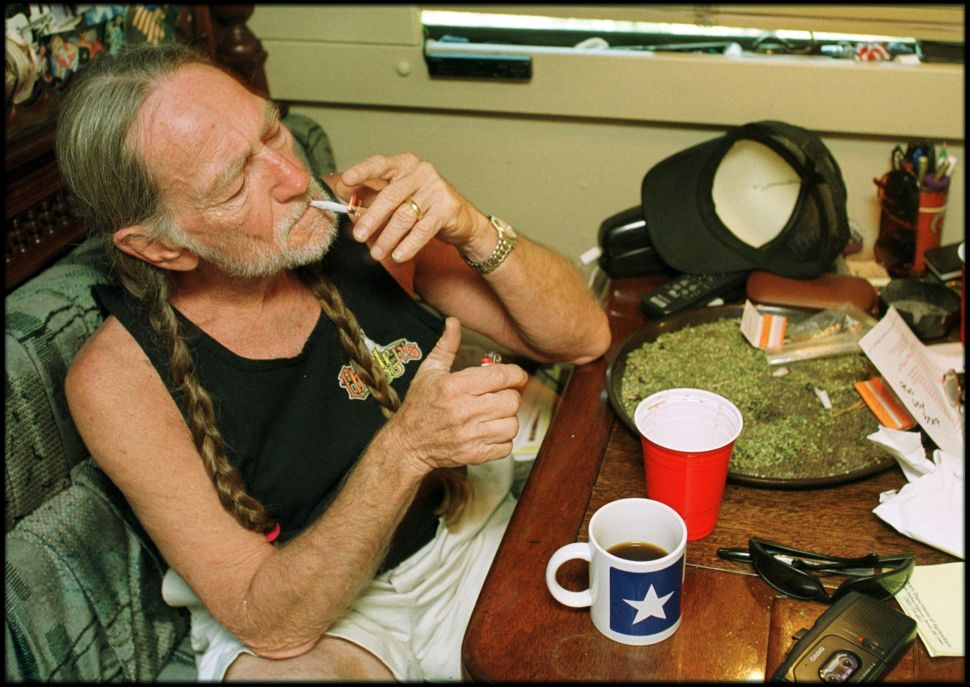 American country singer Willie Nelson takes a drag off a joint while relaxing at his home in Texas.