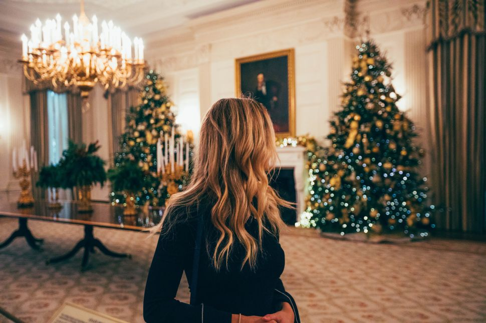 A woman looks at a Christmas tree.