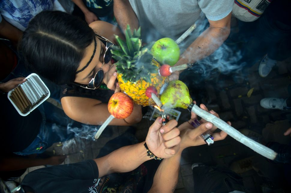 A woman smokes marijuana in a pineapple during a rally demanding its legalization.