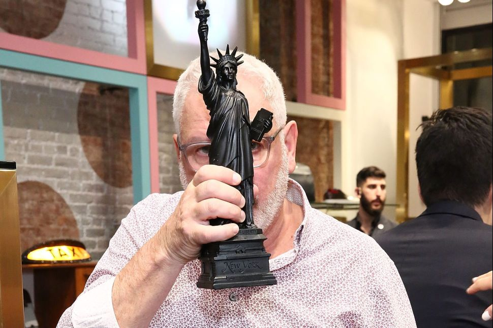 Ray Kelvin obscures his face with a mini-size Statue of Liberty at the Ted Baker Wooster VIP Event on September 22, 2016 in New York City.