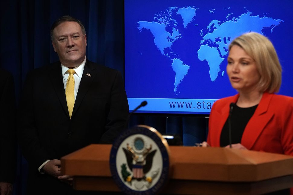 Secretary of State Mike Pompeo listens as State Department spokesperson Heather Nauert speaks during a press event.