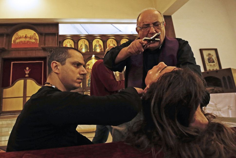 Father Elias Rahal, 68, performs an exorcism ritual on a woman at a church in Lebanon on April 19, 2018.