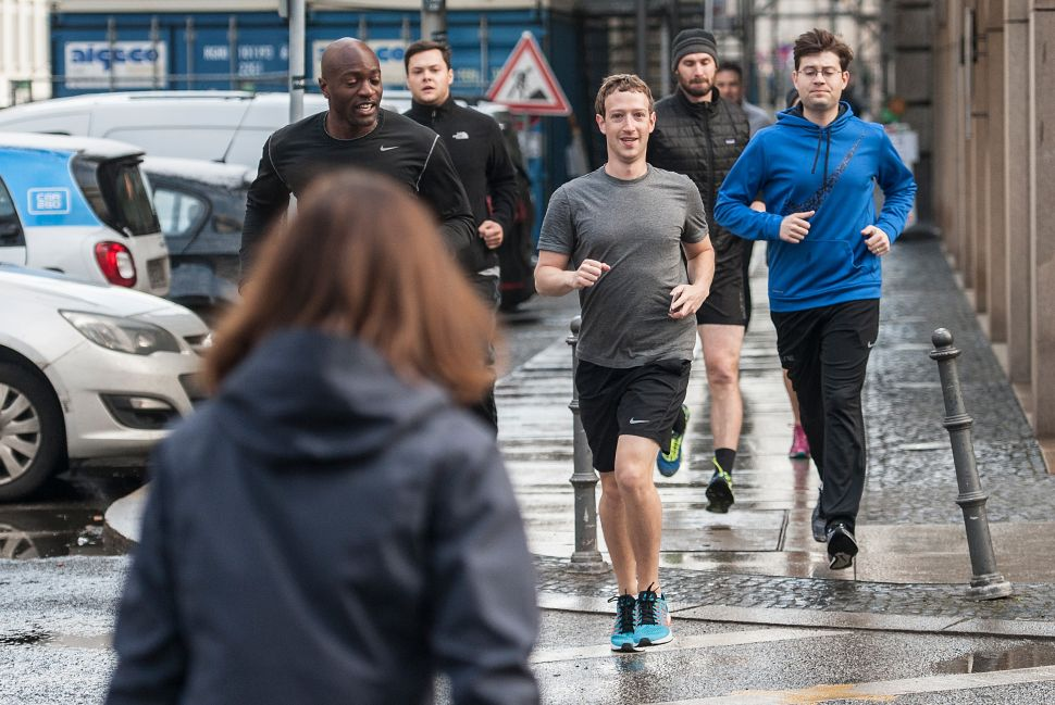 Facebook founder Mark Zuckerberg (C) runs with bodyguards in Berlin, Germany, on February 25, 2016.