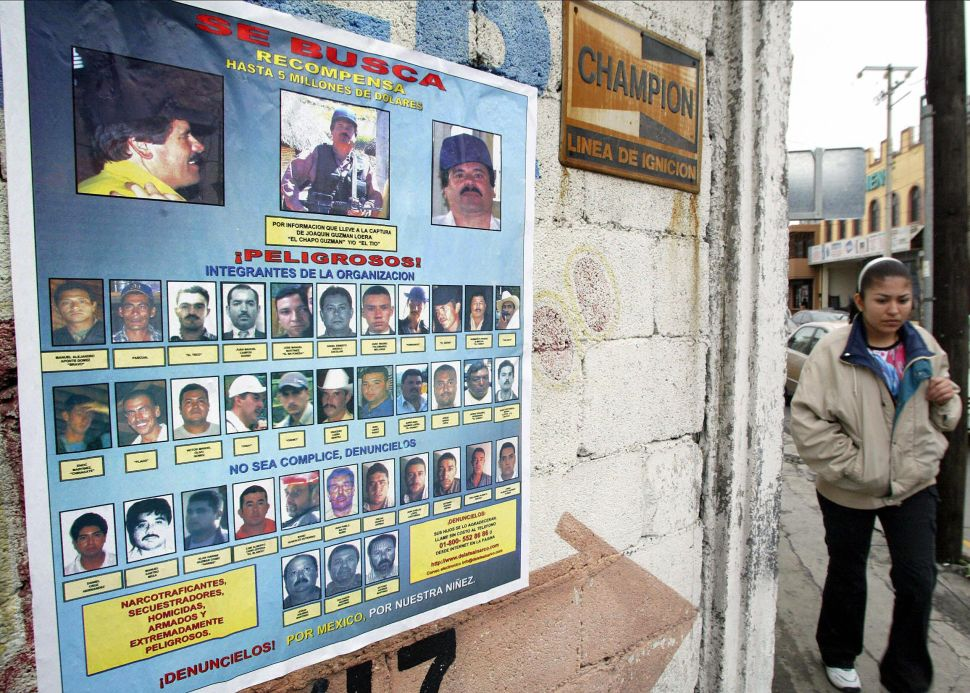 A woman walks past a poster offering rewards of up to $5 million for information leading to the arrest of 36 members of the Sinaloa Cartel.