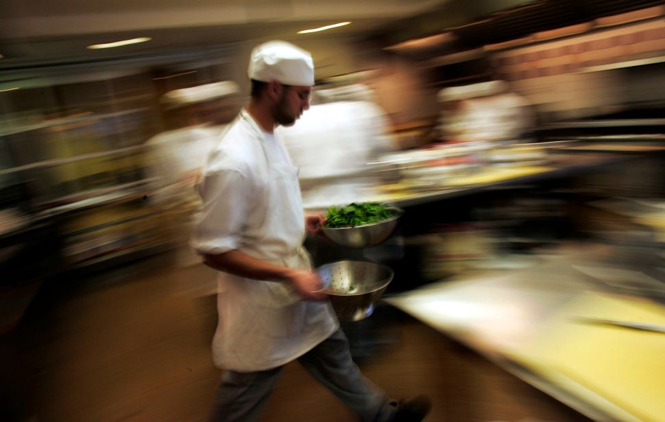 A culinary student rushes through the kitchen with greens during a class for aspiring professional chefs.