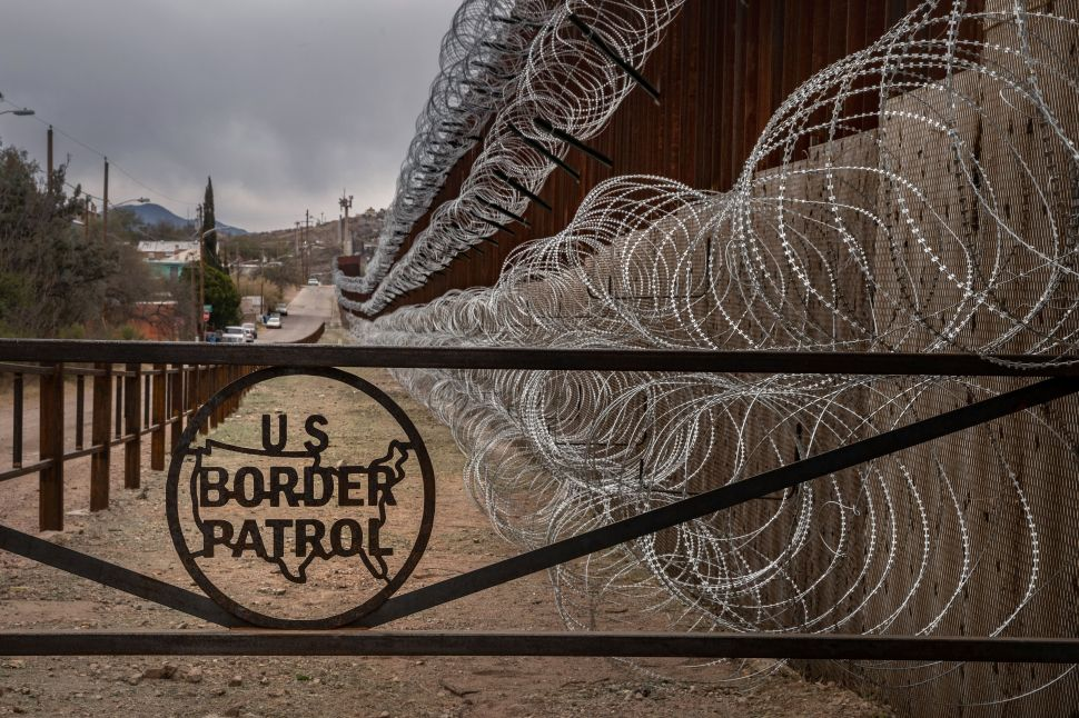 A metal fence marked with the U.S. Border Patrol sign prevents people to get close to the barbed/concertina wire covering the U.S.-Mexico border fence, in Nogales, Ariz., on February 9, 2019.