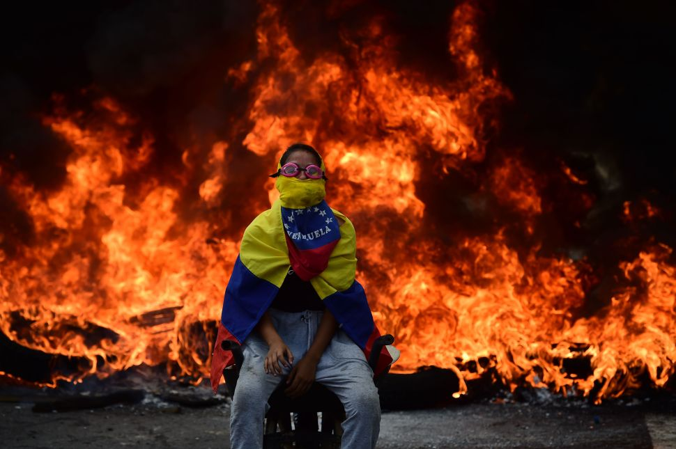 A Venezuelan opposition activist is backdropped by a burning barricade during a demonstration against President Nicolas Maduro in Caracas, on April 24, 2017.