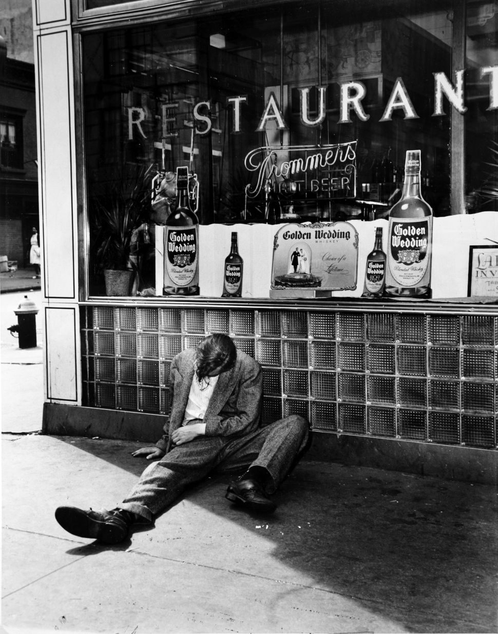 A man sits collapsed in a drunken stupor outside a licensed restaurant.