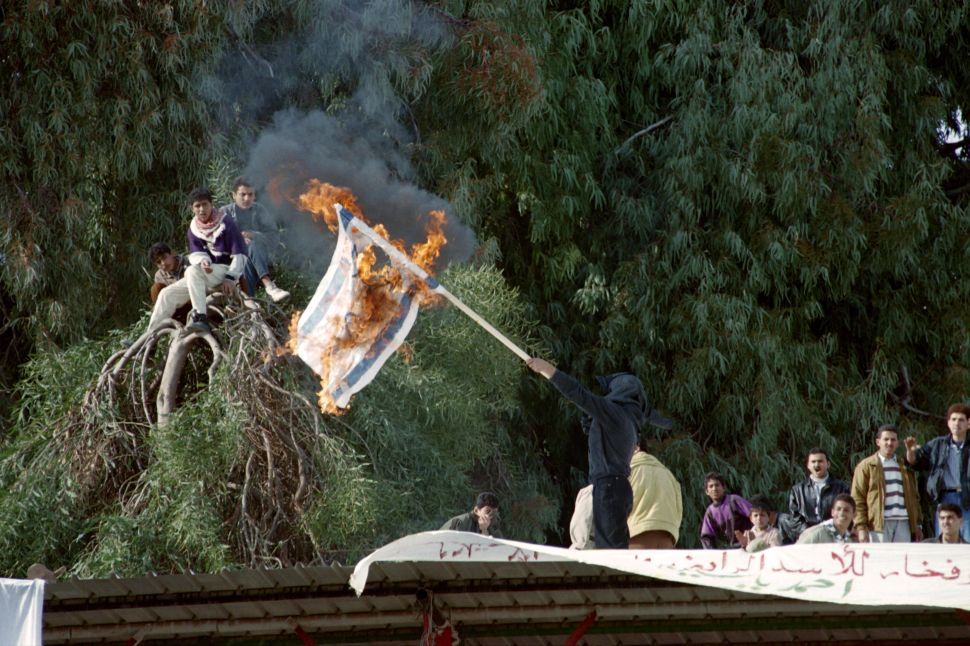 A member of the Palestinian Islamic movement Hamas burns the Israeli flag on the roof of a building during a rally in Gaza City on January 12, 1996.