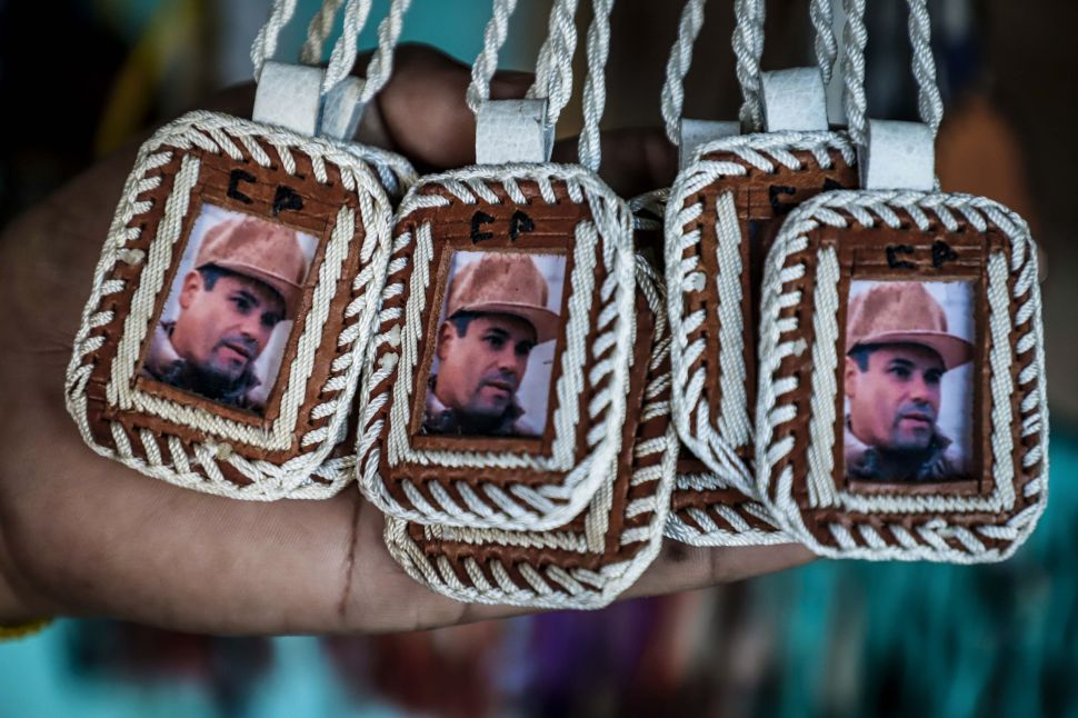 """Pendants bearing the image of Mexican drug lord Joaquin """"El Chapo"""" Guzman, are displayed for sale at the narco-saint Jesus Malverde chapel in Culiacan, Sinaloa state in northwest Mexico, on February, 19, 2018."""