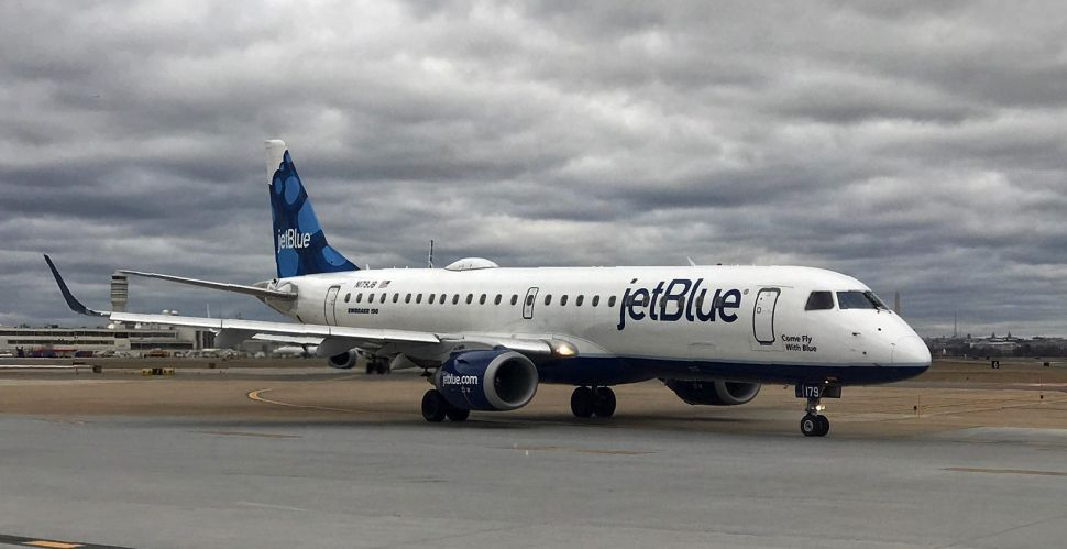 A JetBlue airplane sits on the tarmac waiting for take off.
