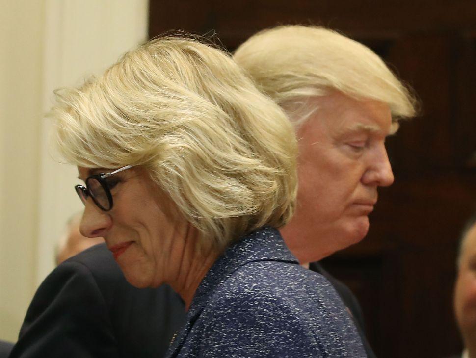 President Donald Trump stands with Education Secretary Betsy DeVos.