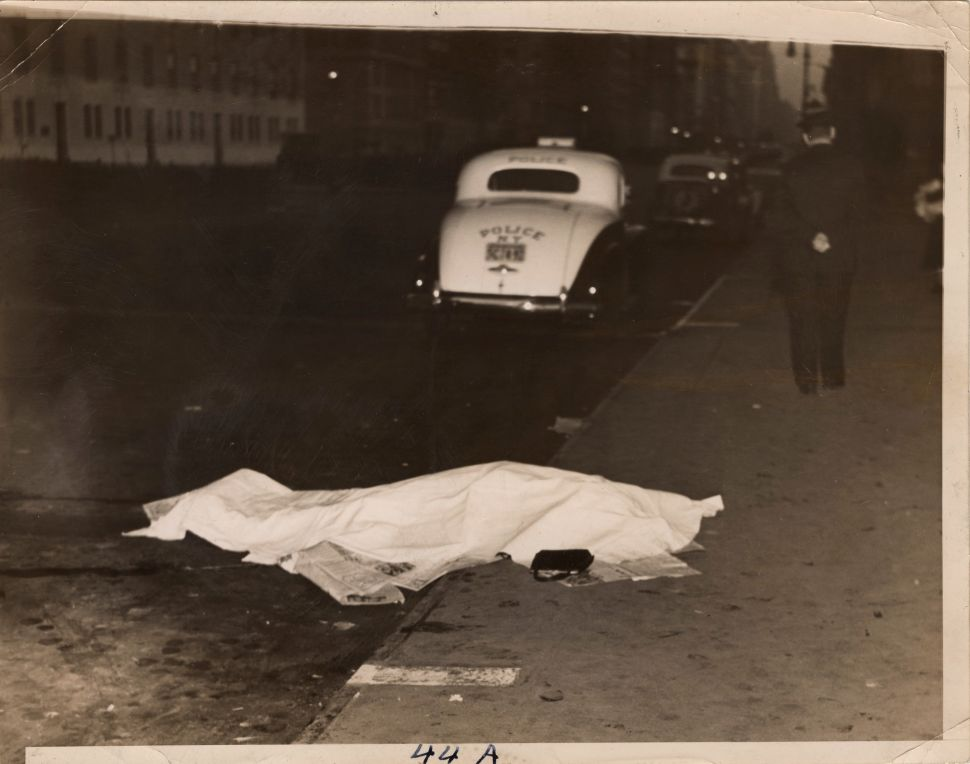 The body of a young woman who jumped from a car and was killed lies on the curb covered by newspapers and a sheet as a policeman walks away with his hands behind his back, New York, 1938.