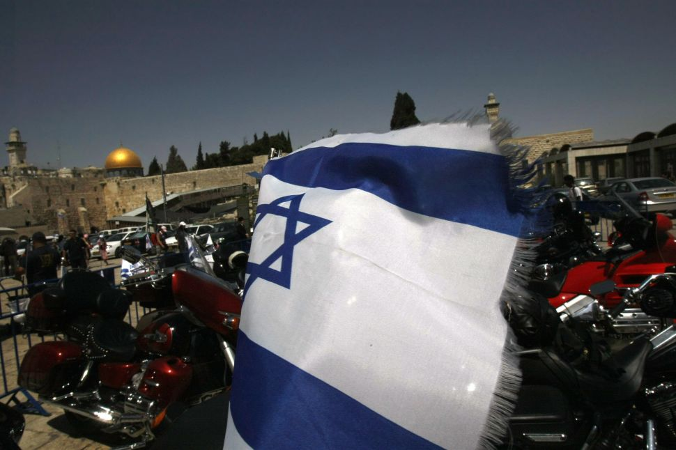 Backdropped by the Western Wall and the Dome of the Rock, an Israeli flag flutters from the back of a Harley Davidson motorcycle in Jerusalem on May 4, 2008.