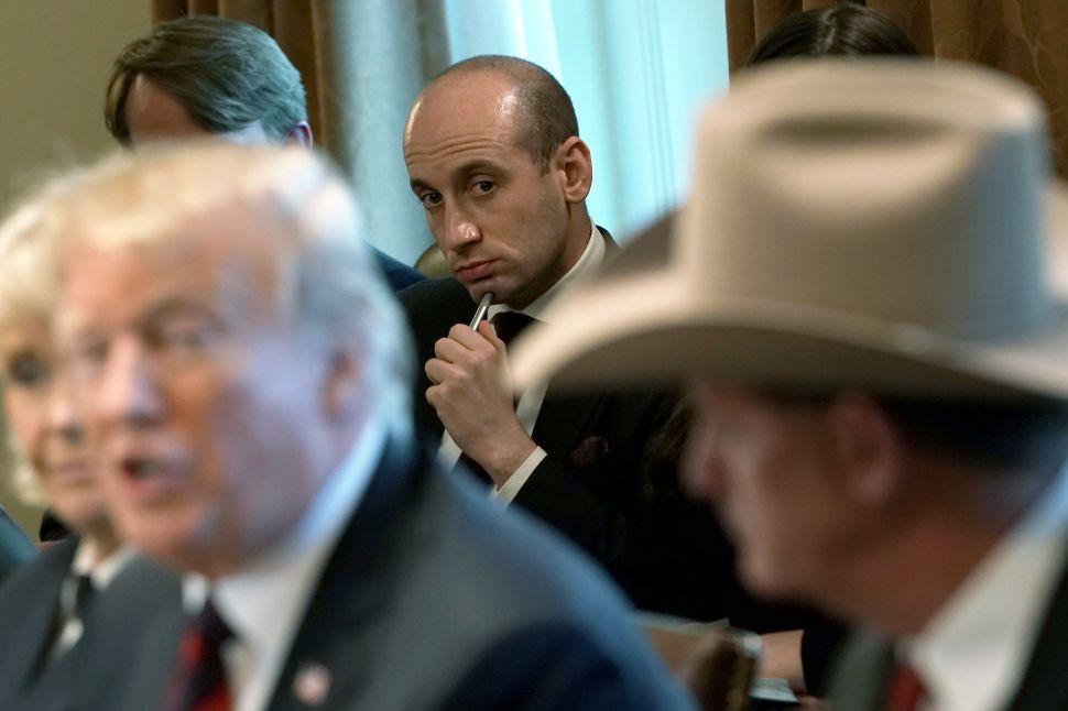 President Donald Trump speaks as Senior Advisor to the President Stephen Miller (C) listens.