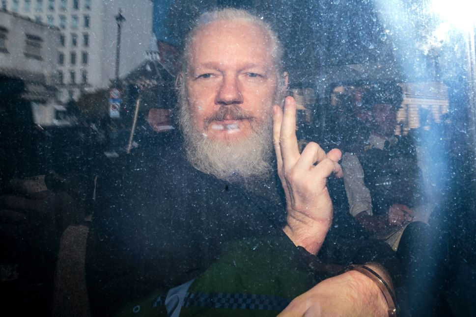 Julian Assange gestures to the media from a police vehicle.