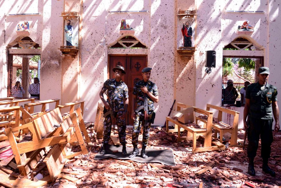 Sri Lankan soldiers look on inside the St Sebastian's Church at Katuwapitiya in Negombo on April 21, 2019, following a bomb blast during the Easter service that killed tens of people. A series of eight devastating bomb blasts ripped through high-end hotels and churches holding Easter services in Sri Lanka, killing nearly 160 people, including dozens of foreigners.