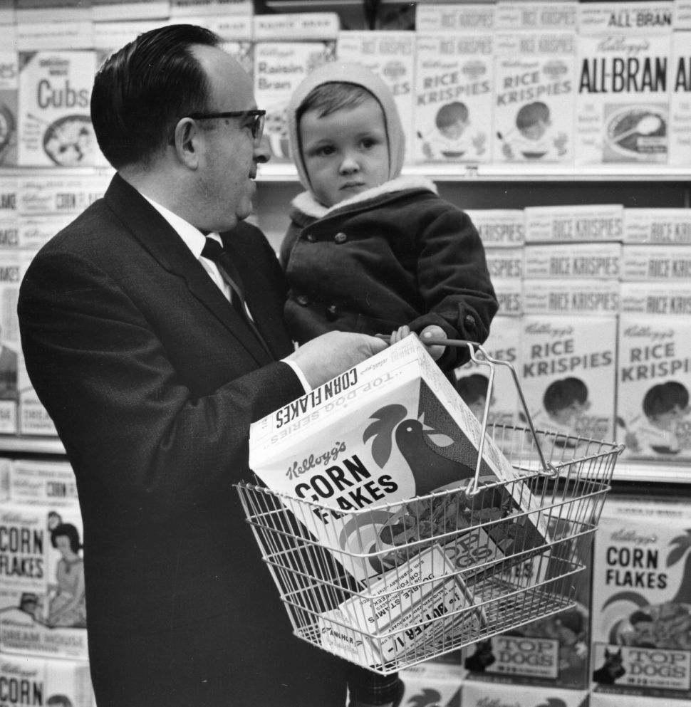 A father holds his baby and Kellogg's Cornflakes, whilst shopping at a Foodtown Supermarket in Lewisham, London on March 4, 1974.