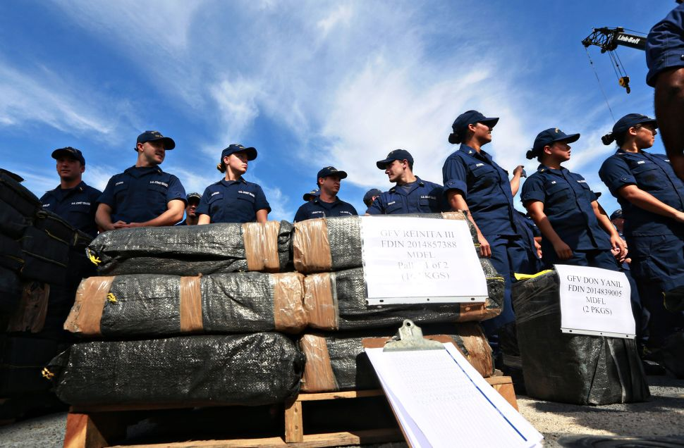 U.S. Coast Guardsmen stand aboard the Cutter Boutwell with piles of confiscated cocaine, seized during 18 different interdictions off the coast of Central and South America, on October 6, 2014 in San Diego, California.