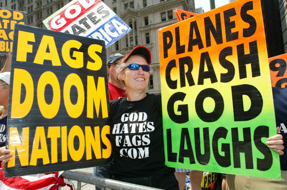 Shirley Phelps holds up signs as she joins fellow members of the Westboro Baptist Church as they protest across the street from Ground Zero on July 4, 2004 in New York City.