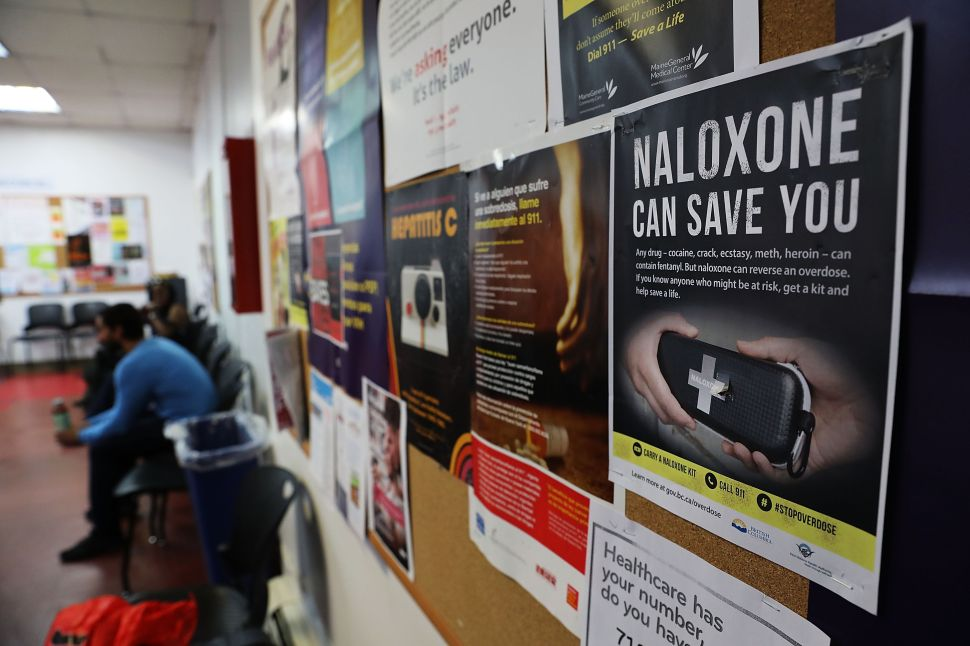 A sign for naloxone hangs on a wall as students learn to put together a naloxone spray gun in a class on opioid overdose prevention.