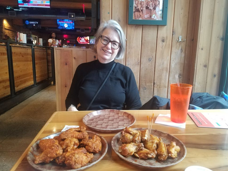 The author's mother enjoying wings with her son at Hooters on Mother's Day.
