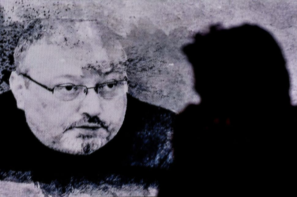 A man passes in front of a screen showing Jamal Khashoggi during a commemoration event on November 11, 2018 in Istanbul.
