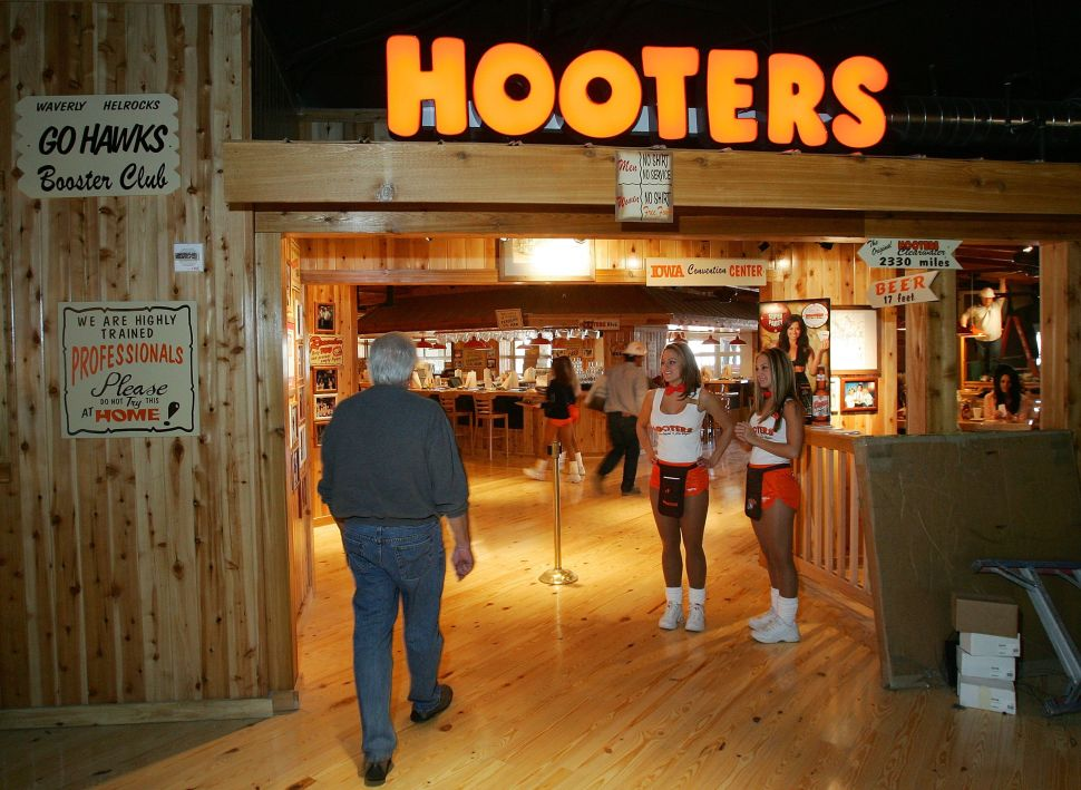 A man enters a Hooters restaurant as waitstaff greet him at the door.