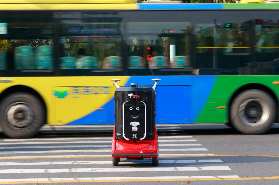 A JD.com unmanned delivery robot is seen crossing a street on November 12, 2018 in Tianjin, China.