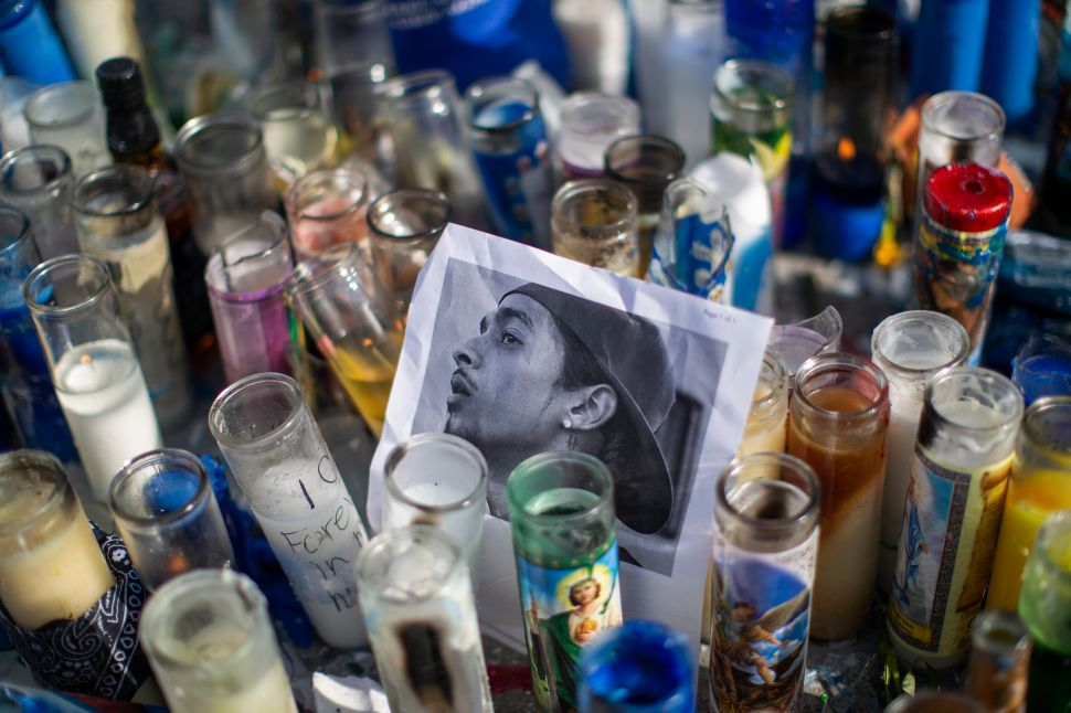 A photo of rapper Nipsey Hussle, 33, is seen among candles as people gather to mourn him on April 1, 2019 in Los Angeles, California.