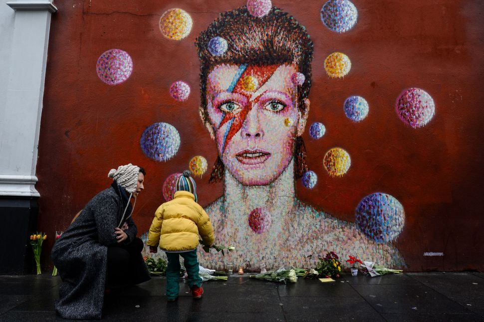 Floral tributes are left beneath a mural of British singer David Bowie, painted by Australian street artist James Cochran (AKA Jimmy C), following the announcement of Bowie's death, in London on January 11, 2016.