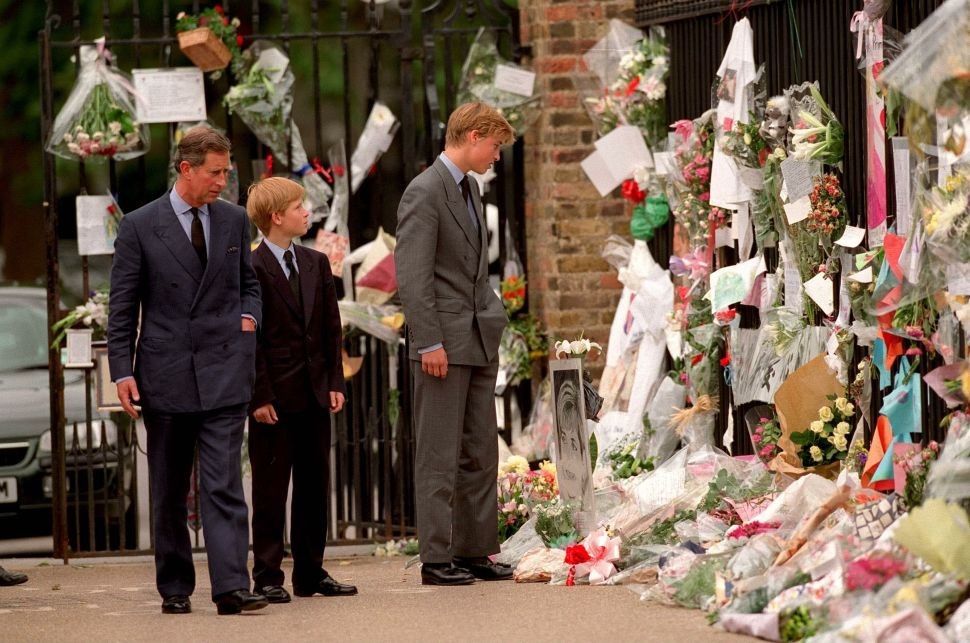 The Prince of Wales, Prince William and Prince Harry look at floral tributes to Diana, Princess of Wales, outside Kensington Palace on September 5, 1997 in London, England.