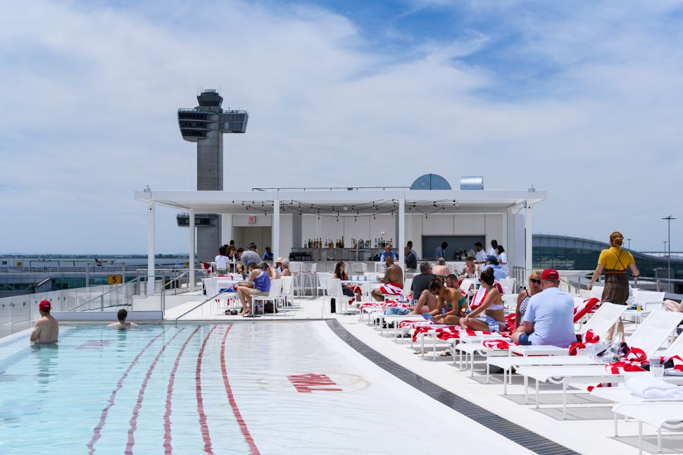 People lounging beside the rooftop pool at JFK airport's TWA Hotel.