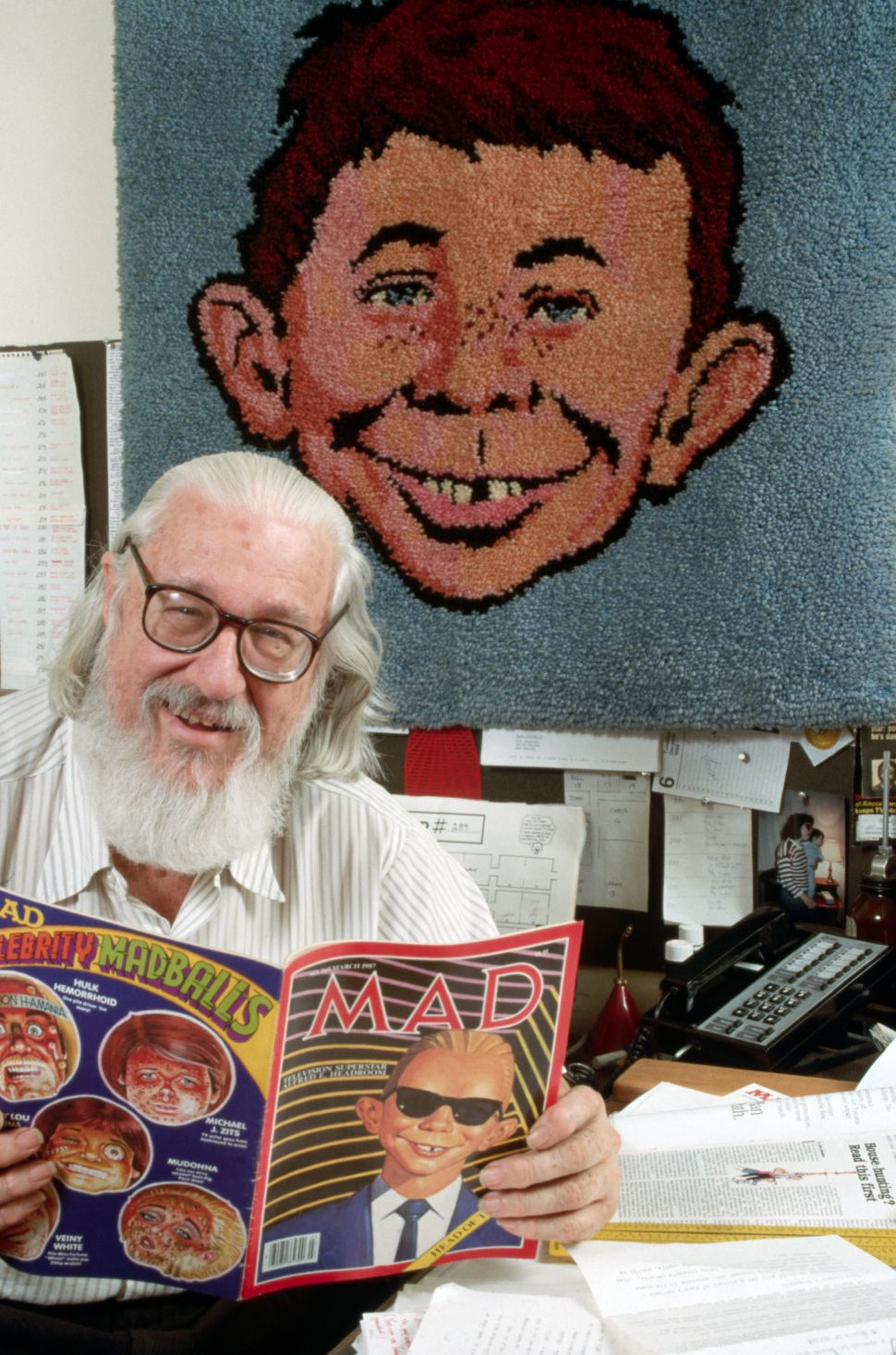 Publisher William Gaines reads a copy of Mad magazine.