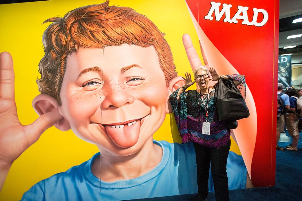 Attendee Judith Hawkins poses next to a display at the Mad magazine booth at Comic-Con Preview Night on July 20, 2016 in San Diego, California