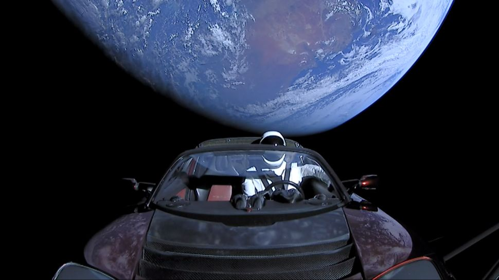 "In this handout photo provided by SpaceX in February 2018, a Tesla Roadster launched from the Falcon Heavy rocket with a dummy driver named ""Starman"" heads toward Mars."