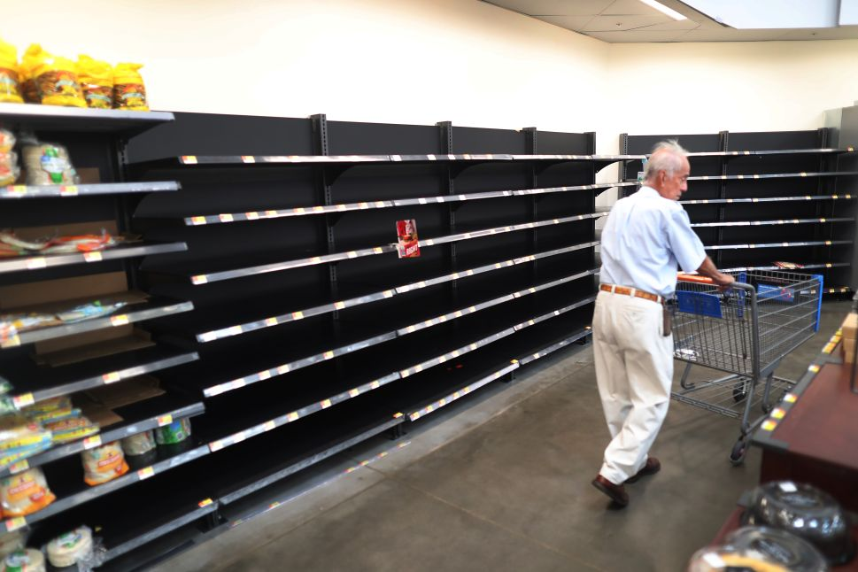 A shopper walks past the empty bread shelves in a Walmart store as people stock up before the possible arrival of Hurricane Dorian on August 30, 2019 in Boynton Beach, Florida.