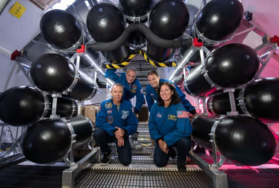NASA astronauts participating in the B330 ground test pose next to the inflation tanks inside the Bigelow testing unit.