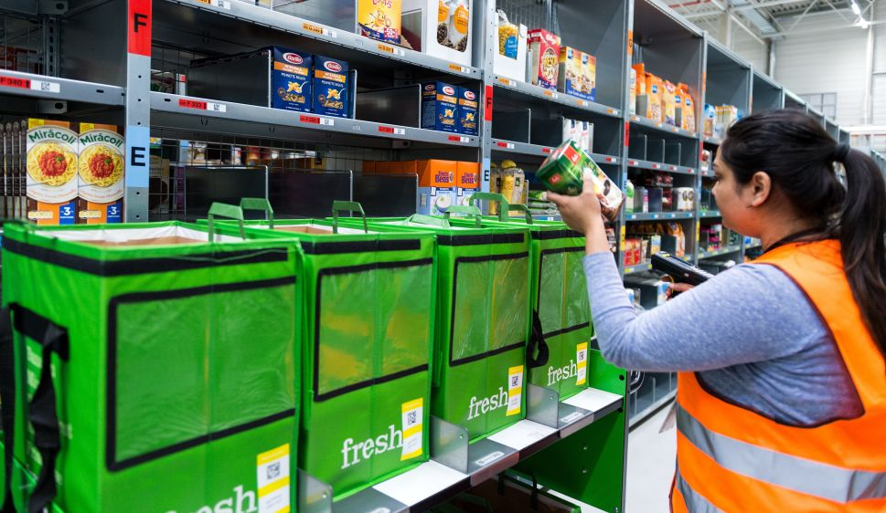 An employee of grocery delivery service Amazon Fresh scans ordered products.