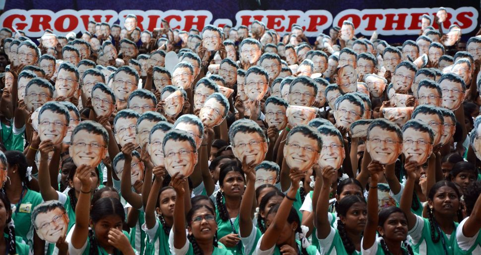 Indian schoolchildren hold masks with the face of Bill Gates.