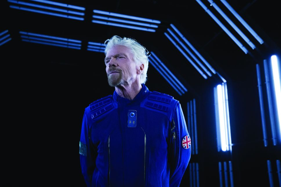 Virgin Galactic founder Richard Branson demonstrate Under Armour's custom made spacesuit.