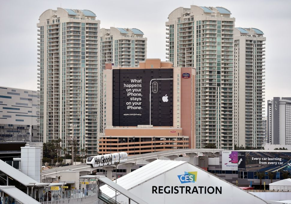 A monorail train featuring a Google ad passes by a billboard advertising Apple's iPhone security during CES 2019 on January 07, 2019 in Las Vegas, Nevada.