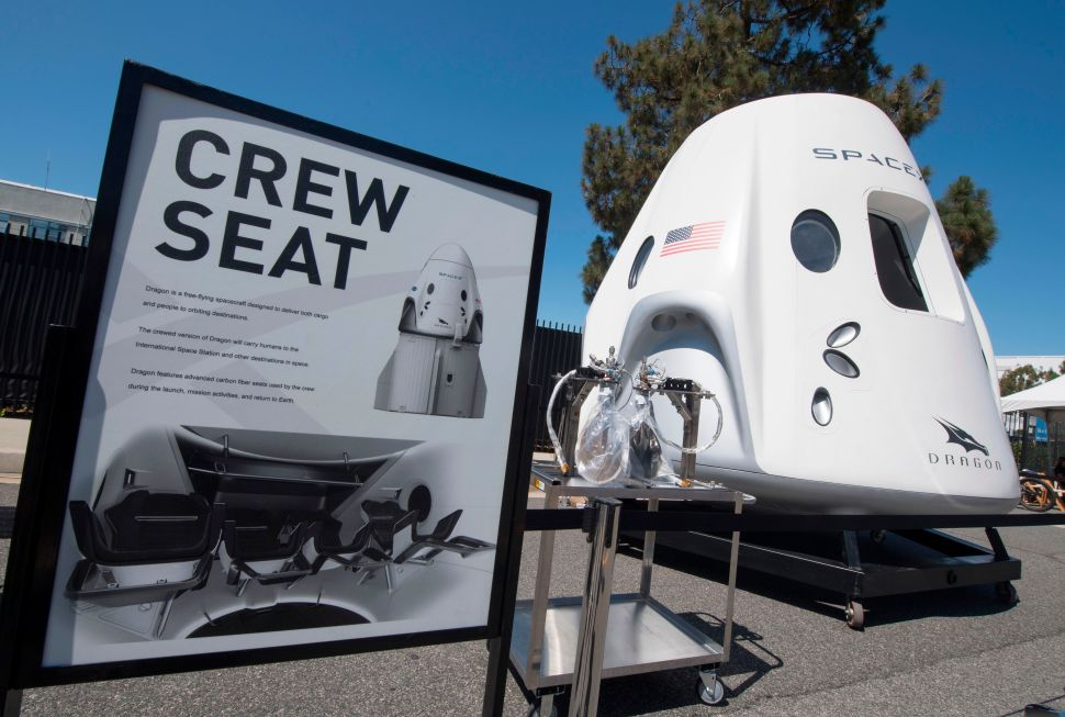 The SpaceX Dragon spacecraft which is designed to carry people and cargo to orbiting destinations, such as space stations, is displayed at the SpaceX headquarters in Los Angeles on July 21, 2019.