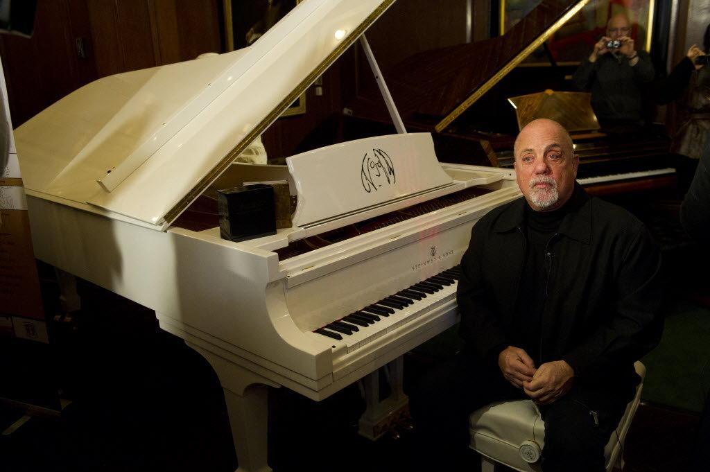 Billy Joel sits at a 'John Lennon' piano at Steinway Hall (Credit: Associated Press)